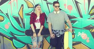 Trendy young skateboarders standing chatting. Leaning against a colorful graffiti wall with a young woman in a baseball cap and handsome young man in sunglasses stock video