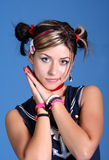 Trendy young woman. A young woman makes a cutesy pose, putting her palms together at the side of her head. Her hair is styled into 2 buns and she is wearing royalty free stock photos