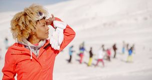Trendy young woman at an alpine ski resort. Standing looking off to the right with a thoughtful expression and tourists visible on the snow behind her stock video