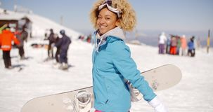 Trendy young woman carrying her snowboard. Trendy young woman with a fun afro hairstyle carrying her snowboard at a ski resort standing sideways looking at the stock video