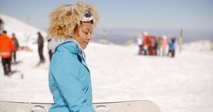 Trendy young woman carrying her snowboard. Trendy young woman with a fun afro hairstyle carrying her snowboard at a ski resort standing sideways looking at the stock footage