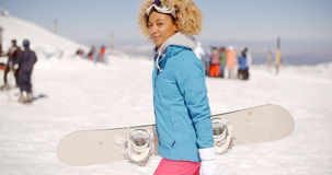 Trendy young woman carrying her snowboard Stock Photo