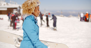 Trendy young woman carrying her snowboard Stock Images