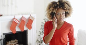 Trendy young woman chatting on her mobile at Xmas. Trendy young African American woman chatting on her mobile phone at Christmas standing in a decorated living stock video