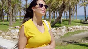 Trendy young woman checking her watch. Trendy young woman wearing sunglasses checking her watch to see the time as she walks along a tropical seafront promenade stock footage