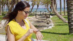 Trendy young woman checking her watch. Trendy young woman wearing sunglasses checking her watch to see the time as she walks along a tropical seafront promenade stock video