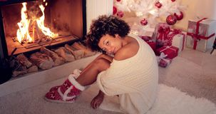 Trendy young woman in Christmas booties. Relaxing in front of a burning fire in front of the tree and gifts on the living room floor stock footage