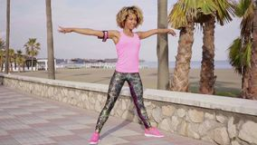 Trendy young woman doing aerobics exercises. Trendy slender young woman in pink and black sportswear standing on a waterfront promenade doing aerobics exercises stock footage