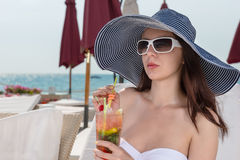Trendy young woman drinking a tropical cocktail Stock Image