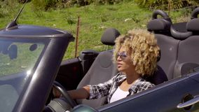 Trendy young woman driving her cabriolet. With the top down along a rural road in the summer sun stock video