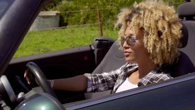 Trendy young woman driving a sports car. On a rural road  close up head and shoulders side view stock video footage
