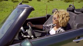 Trendy young woman driving a sports car. On a rural road  close up head and shoulders side view stock video