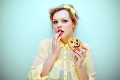 Trendy young woman eating a smiling chocolate chip cookie. Royalty Free Stock Photo