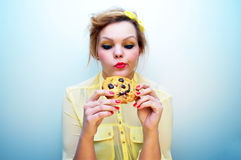 Trendy young woman eating a smiling chocolate chip cookie. Royalty Free Stock Photos