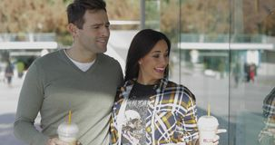 Trendy young woman exclaiming and pointing. At merchandise in a store window as she and her boyfriend stroll along enjoying takeaway coffee stock footage