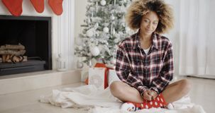 Trendy young woman in front of a Christmas tree. Trendy young African woman sitting cross-legged on a rug in front of a Christmas tree smiling at the camera stock video footage