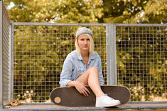 Trendy young woman with her skateboard Stock Photo