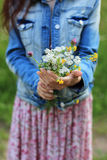 Trendy young woman holding flowers. Trendy young woman holding wild flowers Royalty Free Stock Photo