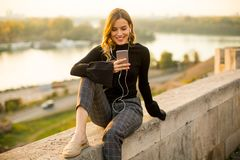 Trendy young woman listening music from smartphone outdoor Stock Images