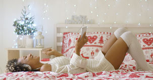 Trendy young woman listening to Christmas music Stock Photos