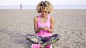 Trendy young woman listening to music on a beach. Sitting cross-legged in the sand selecting a tune from her mobile phone stock video footage