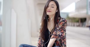 Trendy young woman listening to music in town stock video footage