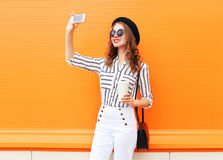 Trendy young woman model taking picture self portrait on smartphone wearing a black hat white pants over colorful orange Royalty Free Stock Photo