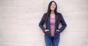 Trendy young woman posing against a wall. Trendy young woman posing against a textured off white wall with hands in pockets smiling at the camera  with copy stock video footage