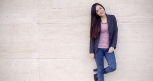 Trendy young woman posing against a wall stock video footage