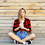 Trendy young woman posing against wooden wall Stock Photography