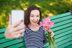 Trendy young woman posing for camera and taking photo of herself Royalty Free Stock Image