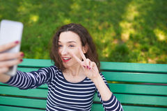 Trendy young woman posing for camera and taking photo of herself Stock Photography