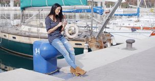 Trendy young woman relaxing at a marine harbour. Sitting on a bollard on the quay checking her mobile phone for messages with a smile stock footage
