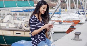 Trendy young woman relaxing at a marine harbour. Sitting on a bollard on the quay checking her mobile phone for messages with a smile stock video