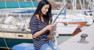 Trendy young woman relaxing at a marine harbour Stock Image