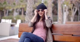 Trendy young woman relaxing on a park bench. Trendy young woman relaxing on a wooden park bench putting on a pair of sunglasses to protect her eyes from the stock video footage