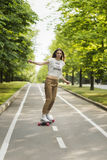 Trendy young woman rides a longboard on a path in a park outdoors in summer. Skateboarding. Outdoors, Royalty Free Stock Images