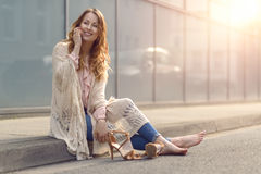 Trendy young woman sitting chatting on her mobile. Trendy young woman sitting on the side of a street with her high heeled shoes off relaxing and smiling while royalty free stock images