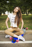 Trendy young woman sitting cross-legged with longboard in park closed her eyes and dreams. Skateboarding. lifestyle Royalty Free Stock Photography