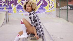 Trendy young woman sitting on a skateboard. Waiting for someone in an urban environment with graffiti stock video