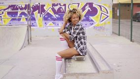 Trendy young woman sitting on a skateboard. Waiting for someone in an urban environment with graffiti stock footage
