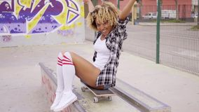 Trendy young woman sitting on a skateboard stock video footage
