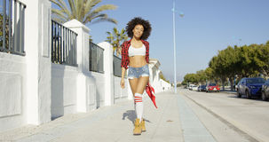 Trendy young woman in skimpy denim shorts Stock Photography