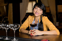 Trendy young woman smiling relaxed at the bar. Horizontal portrait of a trendy young pretty brunette woman smiling relaxed while holding a saucer glass of red stock images