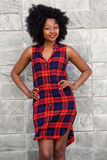 Trendy young woman standing in plaid dress Stock Images