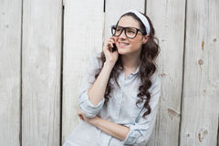 Trendy young woman with stylish glasses having phone call Royalty Free Stock Photo