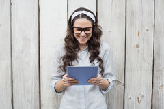 Trendy young woman with stylish glasses using her tablet Stock Images