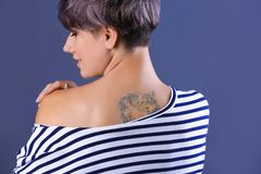 Trendy young woman with tattoo. On color background stock photo