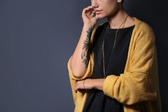 Trendy young woman with tattoo. On grey background, closeup. Space for text royalty free stock photos
