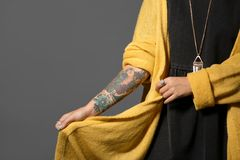 Trendy young woman with tattoo on grey background. Closeup. Space for text royalty free stock photography